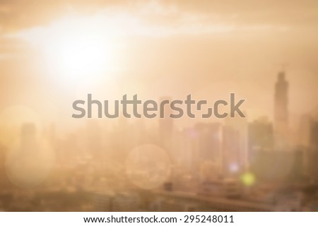 Blurred abstract background of morning gold light view over cityscape of downtown Bangkok with bright sun flare and bokeh in warm color tone: Blur holiday travel backgrounds of urban smokey sunrise  - stock photo