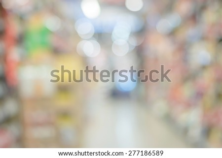 Blurred abstract background of people shopping in super market : Shoppers in grocery store walking in a gangway : Walkway with full with goods and products on shelves in super market  - stock photo
