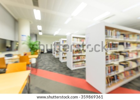 Blurred abstract background of public library interior with aisle of bookshelf with textbooks, literature, seating for students and faculties for reading. Self-study, educational concept/background - stock photo
