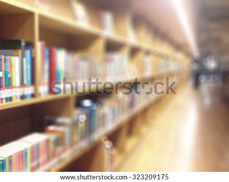 Blurred abstract background of public library interior with aisle of bookshelves and reading area: Blurry perspective view educational study room space w/ book shelves: National library lovers month - stock photo