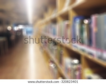 Blurred abstract background of public library interior with aisle of bookshelves, tables, desks and chairs for reading area: Blurry perspective view of educational room indoor space with book shelves - stock photo