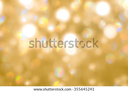 Blurred abstract background of reflective colorful rainbow bokeh of crystal mobile chandelier lamp shiny yellow gold color lighting in vintage colour tone: Sparkling lights of crystal glass reflection - stock photo