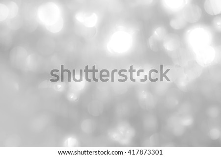 Blurred abstract background of reflective silver magical bokeh of crystal mobile chandelier lamp bright white color lighting in vintage colour tone: Sparkling lights of crystal glass reflection  - stock photo