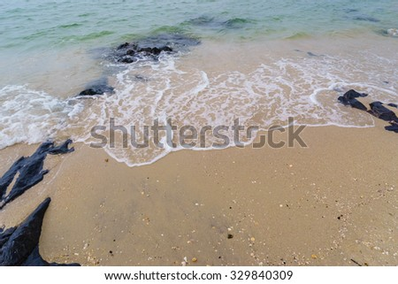 Blurred abstract background of white wave,yellow sand and black stone at Samila beach,Songkhla Southern Thailand.