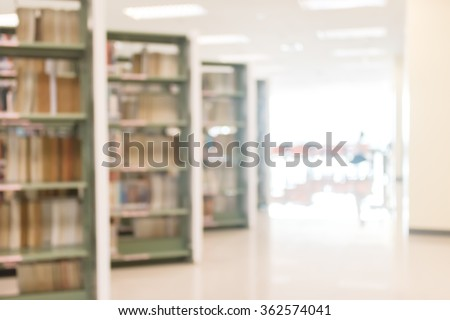 Blurred abstract background view of university student girl in aisle of book shelves in school library: Blurry interior perspective indoor study room with tables, chairs, seats & stacks of books   - stock photo