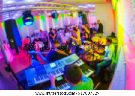 Blurred abstract image of keyboard players and the band and young people dancing during wedding ceremony, with disco lighting in the room casting magenta light