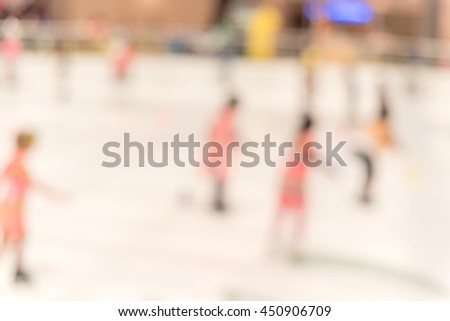 Blurred abstract motion background of parents and kids play indoor ice skating. Defocused of indoor ice skating with people on the ice rink. Natural light from glass roof. - stock photo