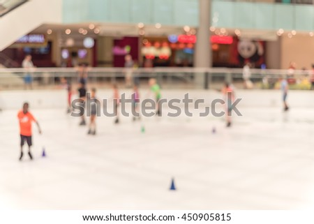 Blurred abstract motion background of parents and kids play indoor ice skating in modern shopping mall. Defocused of indoor ice skating with people on the ice rink. Natural light from glass roof.