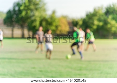 Blurred abstract motion group of young African American and Asian people playing football on green soccer pitch of the park at sunset with warm light at Houston, Texas. Urban healthy lifestyle concept