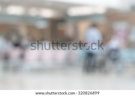 Blurred abstract of waiting hall in hospital lobby in front of cashier and pharmacy dispensary counter with patients and nurses in the area: Blurry bright view of healthcare clinic seating zone - stock photo