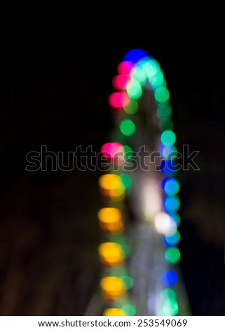 Blurred and colorfull lights of a ferris wheel against a black background - stock photo