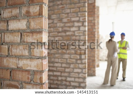 Blurred architect and construction manager at site with focus on brick walls - stock photo