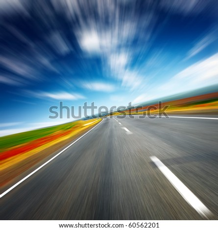 Blurred asphalt road and blue motion blurred sky with clouds - stock photo