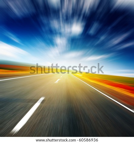 Blurred asphalt road and blue motion blurred sky with clouds and light spot - stock photo