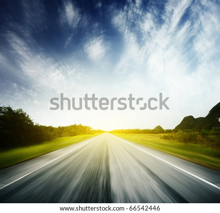 Blurred asphalt road and blue sky with clouds