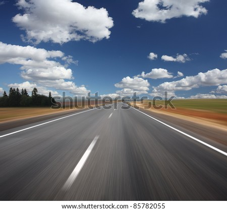 Blurred asphalt road and blue sky with clouds - stock photo