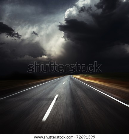 Blurred asphalt road and dark thunder clouds over it - stock photo