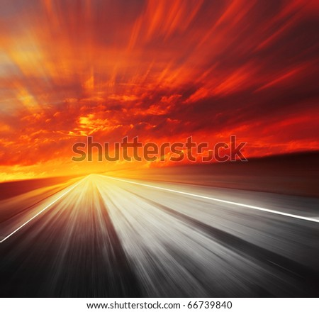 Blurred asphalt road and red clouds - stock photo