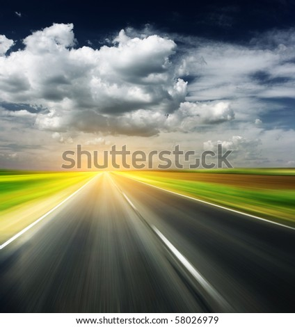 Blurred asphalt road and sky with clouds