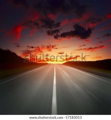 Blurred asphalt road and sky with red clouds - stock photo