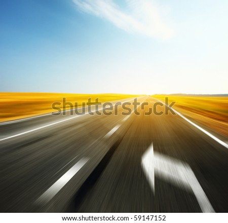 Blurred asphalt road with signs and blue sky - stock photo