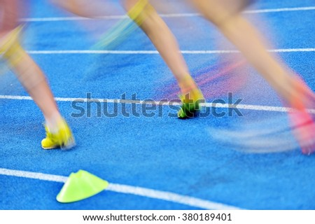 Blurred athletes by a slow camera shutter speed are competing on blue sprint track - stock photo