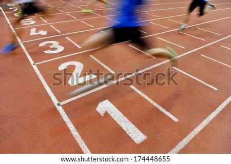Blurred athletes by a slow camera shutter speed are crossing the finish line after sprint track - stock photo