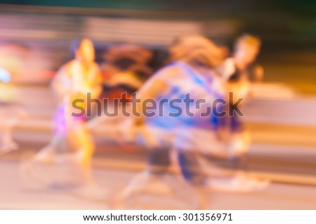 Blurred athletes by a slow camera shutter speed are running the night marathon. Sport background. - stock photo