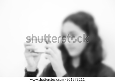 Blurred attractive pretty woman using smartphone for shooting photograph black and white version - stock photo