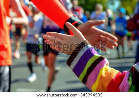 Blurred backgriund: marathon running race, support runners on road, child's hand giving highfive, sport concept  - stock photo