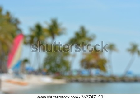 Blurred background abstract image of a beach on the ocean with sailboat, palm trees and a rock jetty. - stock photo