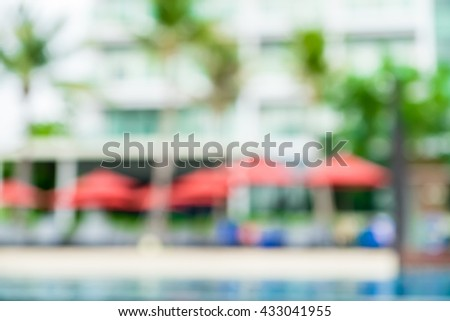 Blurred background,beach umbrella and palm tree at swiming pool at resort. - stock photo