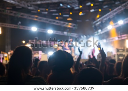 Blurred background : Bokeh lighting in outdoor concert with cheering audience, hands up