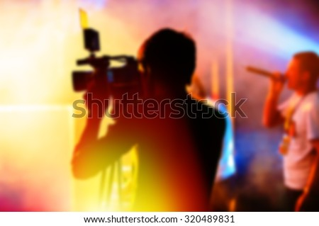 blurred background, cameraman is videotaping the concert
