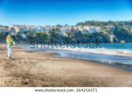 Blurred Background image from a beach with woman walking - stock photo