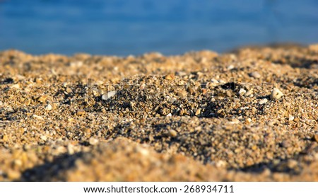 Blurred background image of sea sand and sun. Blurred picture with: partly visible texture of small stones and sand seashore lit by light rays of the evening sun. Beach, seashore. Support of the text. - stock photo