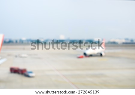 Blurred background : looking through terminal window to see airplane at airport - stock photo
