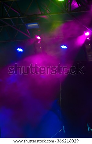 blurred background, many spotlights that illuminate the stage at a concert with fog