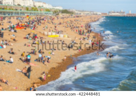Blurred background of a beach with people sunbathing. Aerial view of the coastline with water and waves on the right. Photo taken in Brighton, England. - stock photo