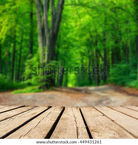 blurred background of autumn forest and brown wooden deck table. Ready for product montage display