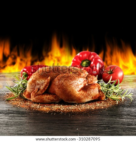blurred background of dark space and fire with vegetables and chicken  - stock photo