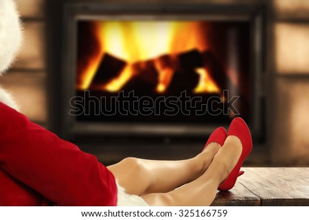 blurred background of fireplace and top place and long legs of woman