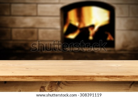 blurred background of fireplace and wooden desk top place for you  - stock photo