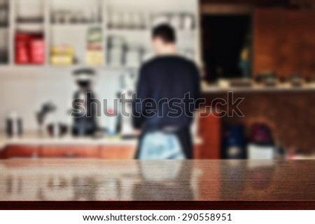 blurred background of interior in bar with barista and dark desk of free space for you  - stock photo