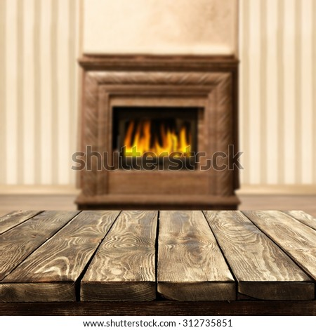blurred background of interior with fireplace and space on wooden  table of brown color and space for you