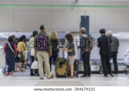 blurred background of people waitting for picking up suitcase on luggage conveyor belt in the airport,Luggage Belt at Airport Terminal with Bags and Cases and Passengers waiting collecting it