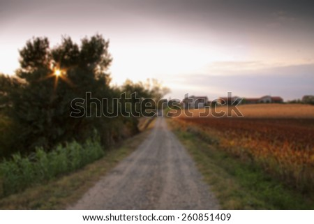 Blurred background of road in the fields, horizontal image - stock photo