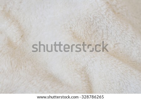 Blurred background of soft light tissue. Beige background of plush fabric - stock photo