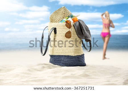 blurred background of summer coast and woman in pink bikini with single big bag and sunglasses and hat  - stock photo