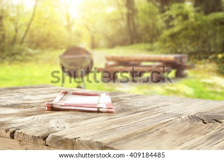 Blurred background of sunny day in old forest with big wooden table and black grill and party time